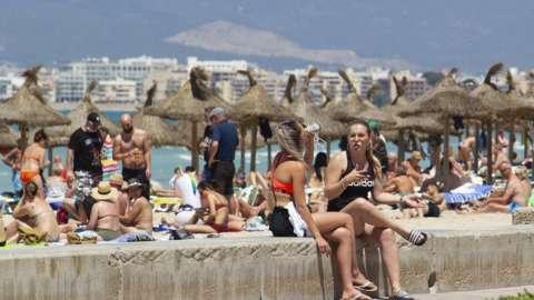 Tourists sit on the promenade at Palma Beach in Palma de Mallorca on June 7, 2021.