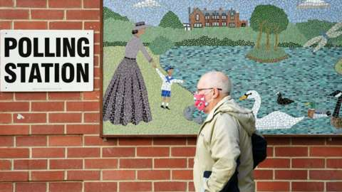 Map in a mask walking passed a polling station sign