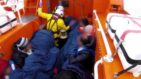A dinghy full of migrants being rescued by the RNLI in the English Channel.