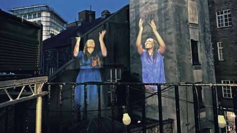 Two women in Sign Night projected on the side of a building