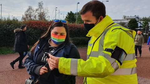 Fan has Covid pass checked by official