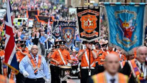 Members of the Orange Order and their supporters march through the city