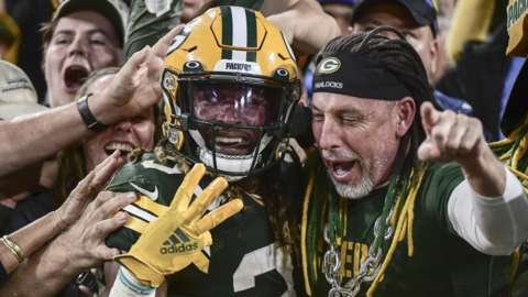 Aaron Jones celebrates a touchdown with a Green Bay Packers fan