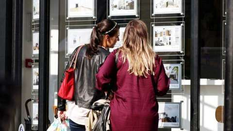 Two women browse an estate agent's window