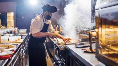 Chef cooking wearing face mask.