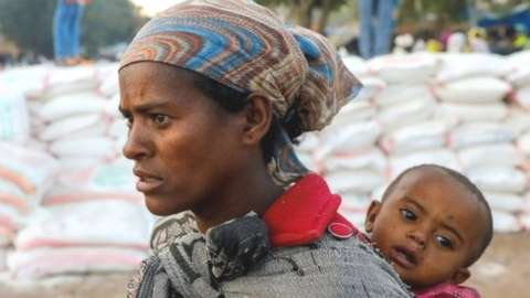 A woman carries an infant in Shire, Tigray region.