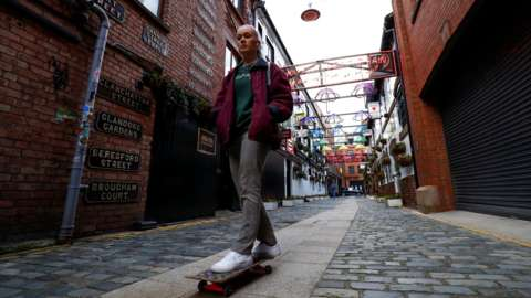 A young woman on a skateboard on a Belfast street