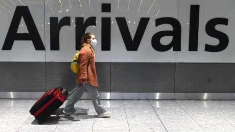 Woman in front of arrivals sign at Heathrow Airport.