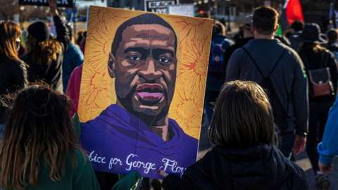 """Two kids hold a poster of George Floyd as demonstrators hold signs and flags during the """"Justice for George Floyd"""" march to the Minnesota State Capitol on March 19, 2021 in Saint Paul, Minnesota."""