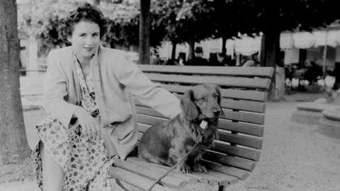 Photo of a woman on a bench with a dog