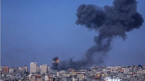Smoke and flames seen rising up after an Israeli airstrike in the northern Gaza strip, 12 May 2021.