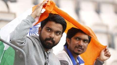 India fans shelter under a flag