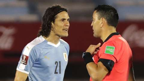 Edinson Cavani argues with the referee following his sending off