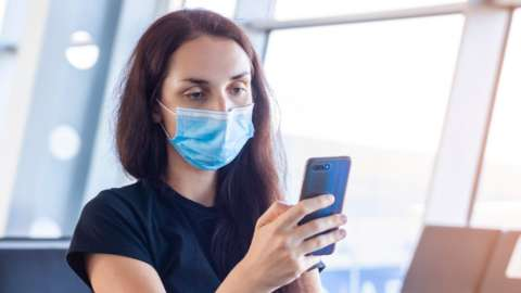 Woman holding a phone in an airport