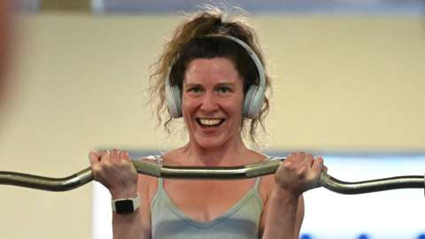 A woman lifts a weight whilst smiling at herself in the mirror