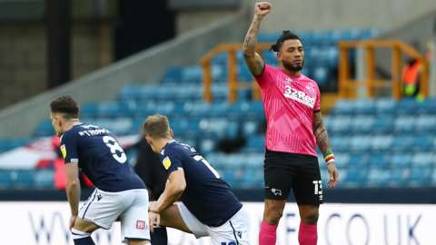 Derby County's Colin Kazim-Richards raises his fist as Millwall players take a knee