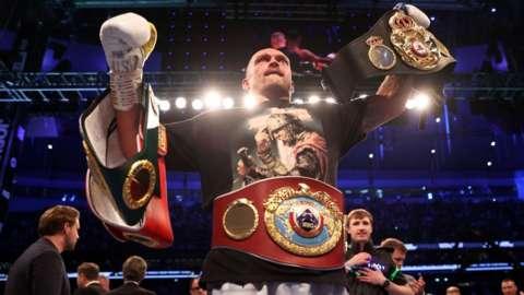 Oleksandr Usyk holds his belts