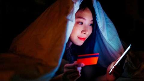 Woman shopping online under a duvet