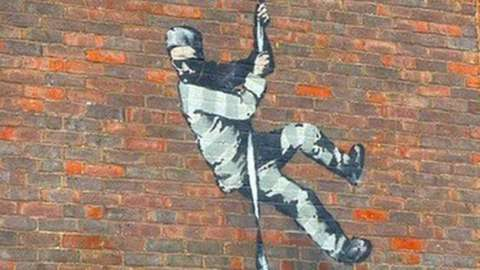 Possible Banksy mural of a prisoner using knotted bedsheets as a rope to lower themself down as if to escape the prison