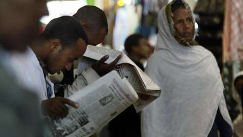 A businesman and customers read a newspaper 14 May 2005 in the old Mercato (market) in Addis Ababa, Ethiopia.
