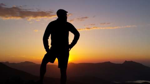A man's silhouette on top of a mountain staring down at a sunset