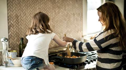 Stock photo of a mother and daughter cooking on a gas cooker