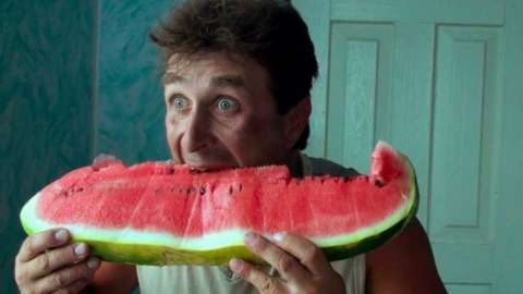 A man eating a watermelon in Life in a Day 2020