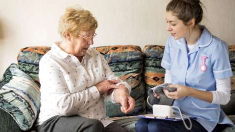 Stock image of a care worker and an elderly client
