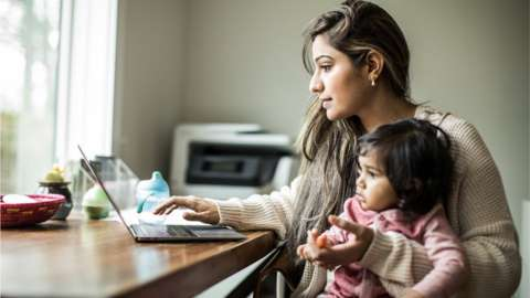 Woman holding a toddler while using a laptop.