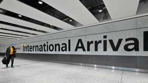Passengers arrive with at the Terminal 5 international arrivals hall at London Heathrow Airport