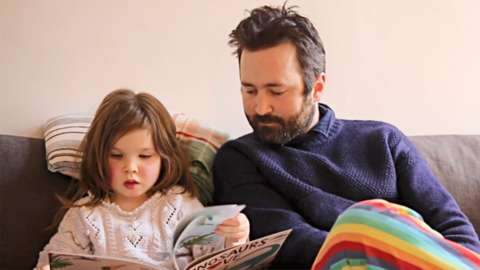 Tom Rosenthal and his daughter Fenn reading their book