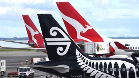 Tails of Qantas and Air New Zealand jets on the tarmac in Sydney.