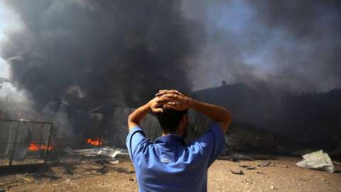A man in front of a burning factory in Gaza
