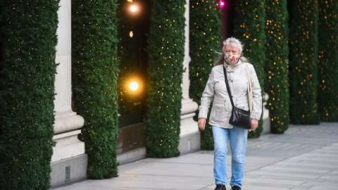A woman wearing a face mask passes Christmas lights outside shops on Oxford Street, London