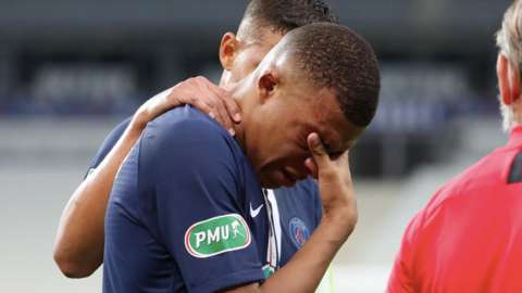 Kylian Mbappe with his head in his hands