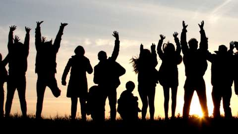 Young people and children silhouetted against a sunset
