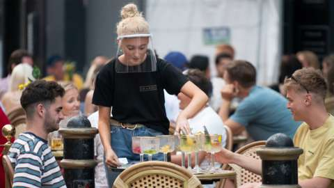 A woman wearing a face visor serves drink outside