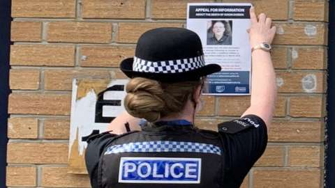 Officer putting up poster at ground