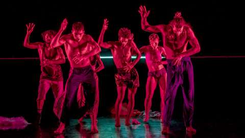 A dance group performing on stage