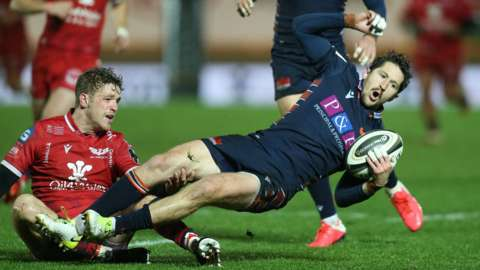 Henry Pyrgos of Edinburgh is tackled by Angus O'Brien of Scarlets