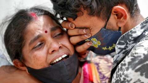 A woman mourns with her son after her husband died due to the coronavirus disease (COVID-19) outside a mortuary of a COVID-19 hospital in Ahmedabad, India, April 20, 2021.
