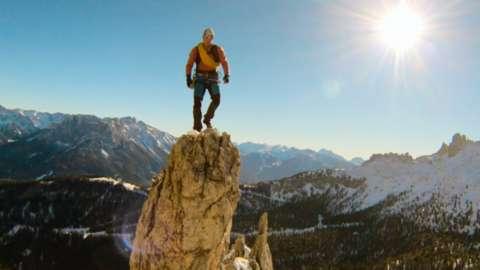 Man standing on top of high peak