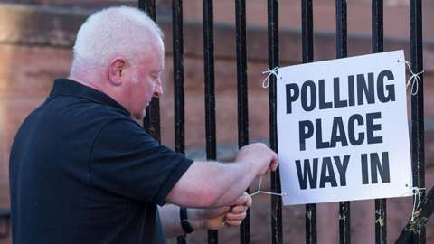 A janitor hangs up signs for a polling station at a school in Glasgow on June 23, 2016.
