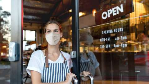 A cafe owner wearing a mask looks out of the front door or her cafe