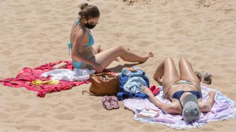 A beachgoer wears her protective mask as she sunbathes