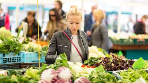 Woman at market stall browsing at tables of vegetables