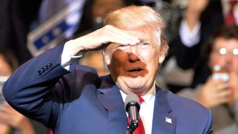 Donald Trump raises his hand to shield his eyes from a bright ray of light
