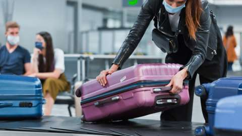 Woman lifting luggage off carousel at airport