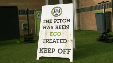 Sign stating 'The pitch has been eco treated, keep off' at the home of Forest Green Rovers