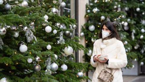 Woman with mask walking past xmas trees